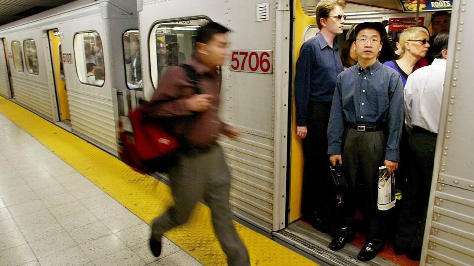 Un passager court et essaie d'entrer dans un wagon de métro.