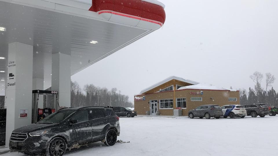 Une voiture est stationnée à côté d'une pompe à essence et un dépanneur est derrière.
