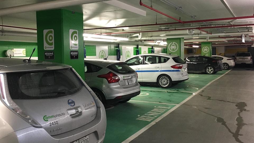 Des voitures électriques garées sur des espaces de stationnement peints en vert.