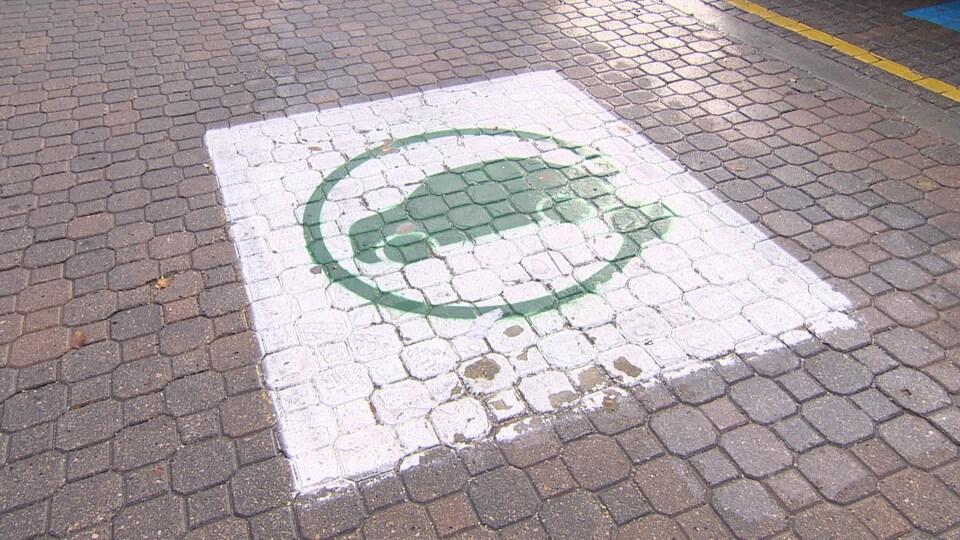 Un rectangle blanc au milieu duquel se trouve le logo d'une auto dans un cercle en vert est peinturé sur le pavé d'un stationnement.