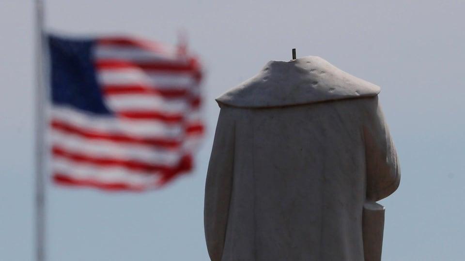 Une statue décapitée et un drapeau américain en arrière-plan