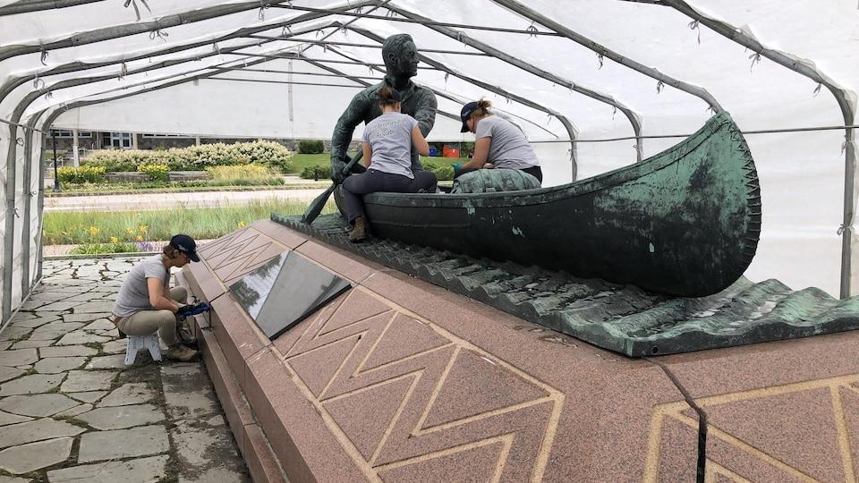 Trois femmes travaillent sur la statue du colonel McCormick avec différents outils.