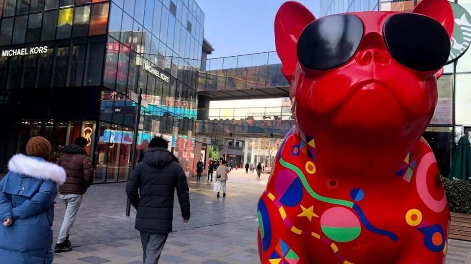 Une immense statue et des passants sur une artère commerciale.
