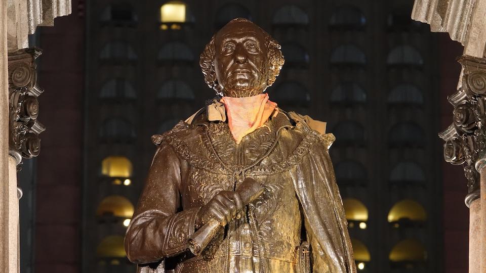 La statue d'un homme, photographiée le soir, est couverte de peinture orange.