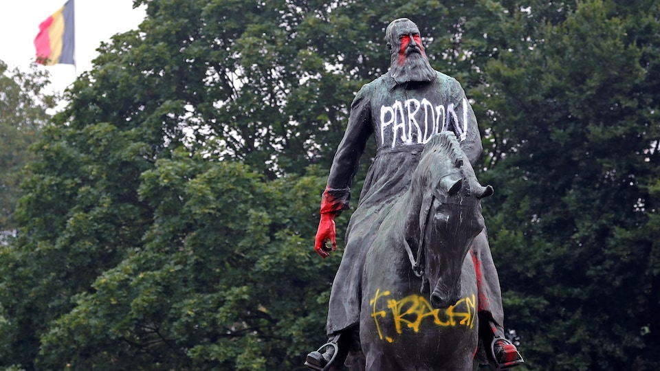 Une statue est marquée de peinture rouge et blanche.