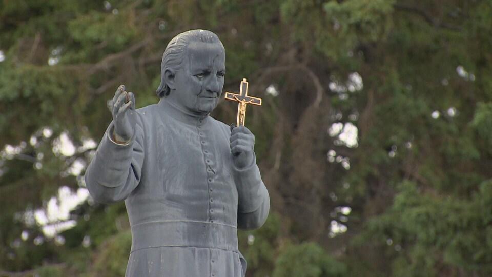 Il tient un crucifix dans sa main gauche.