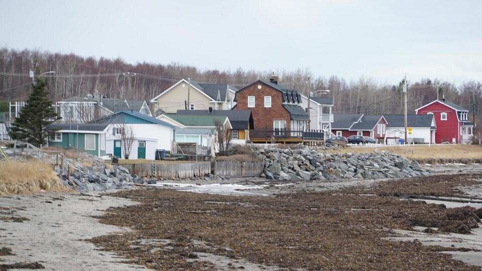 Des maisons en bord de mer séparées de la plage par de grosses roches ou des quais en bois.