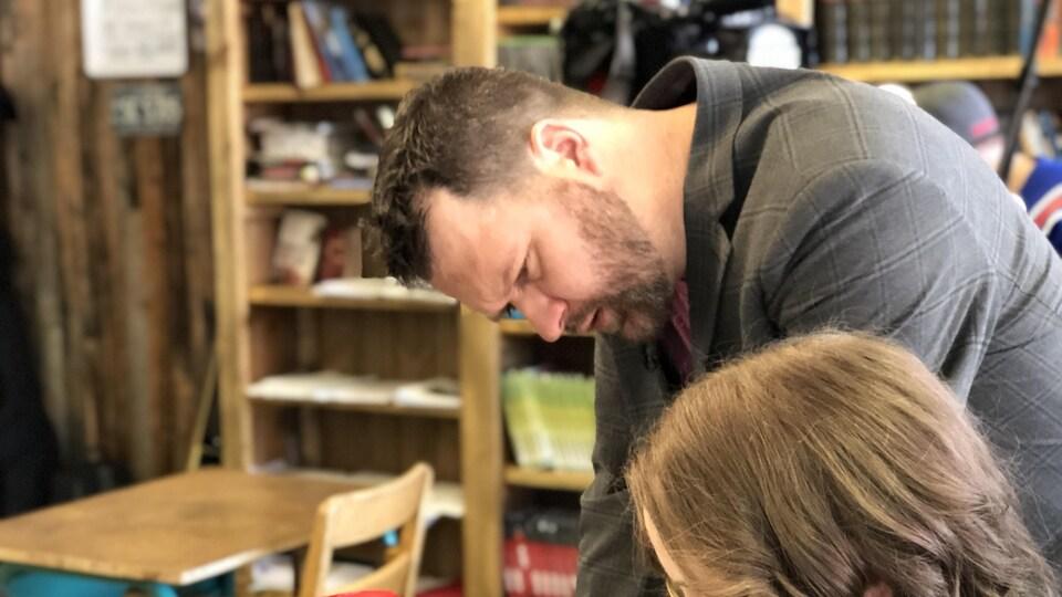 Steeve Girard en train d'aider une élève à son pupitre.