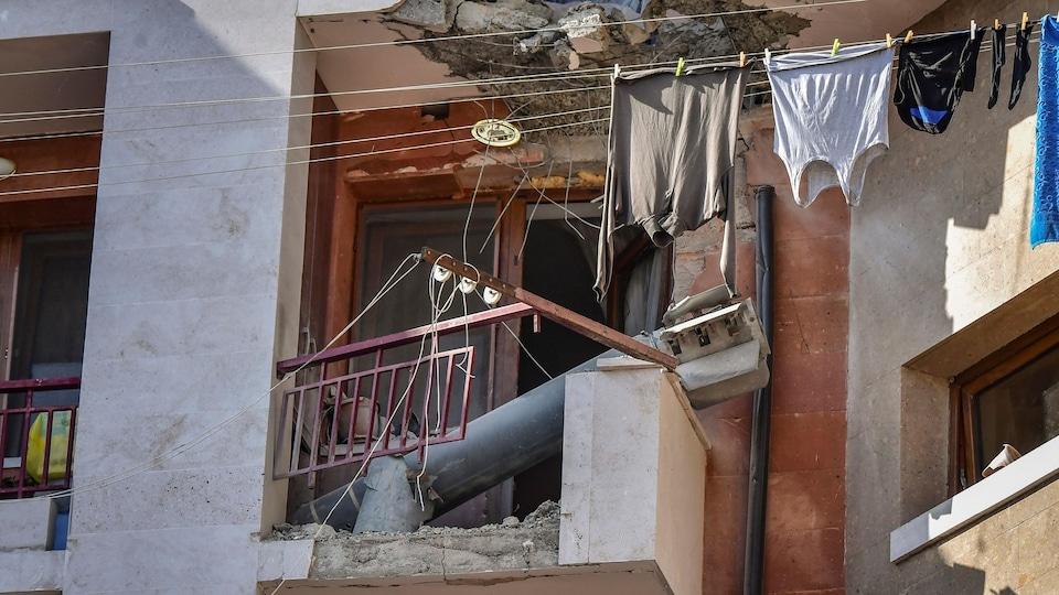 Un long tube de métal repose sur un balcon partiellement détruit.