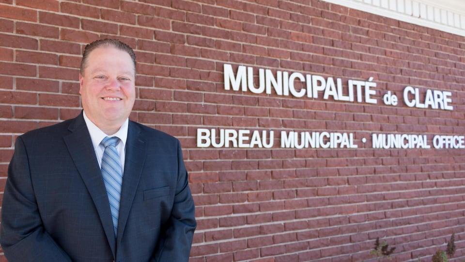 Un homme en complet devant le mur du briques du bureau municipal.