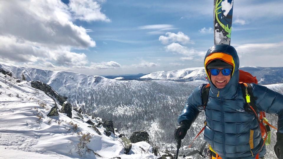Un homme porte un manteau et une capuche. Sur son dos, il porte un sac et des skis. Il est au sommet d'une montagne enneigée.