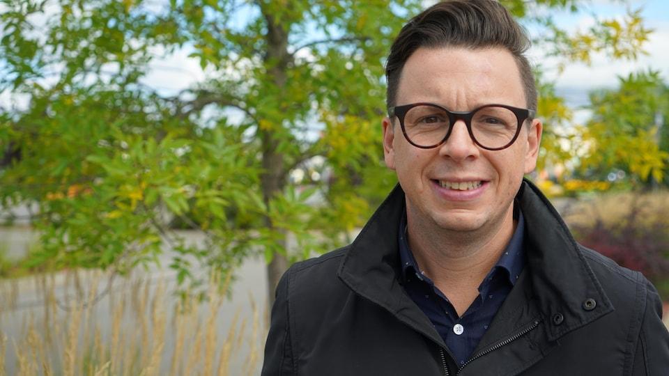 Un homme avec des lunettes et un manteau noir sourit à la caméra devant des arbres aux fleurs jaunes