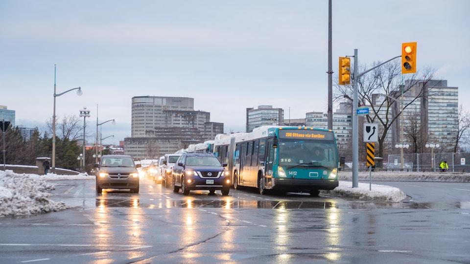 Des voitures et un autobus de la Société de transport de l'Outaouais arrêtés à l'intersection de la rue Wellington et du pont du Portage à Ottawa en hiver.
