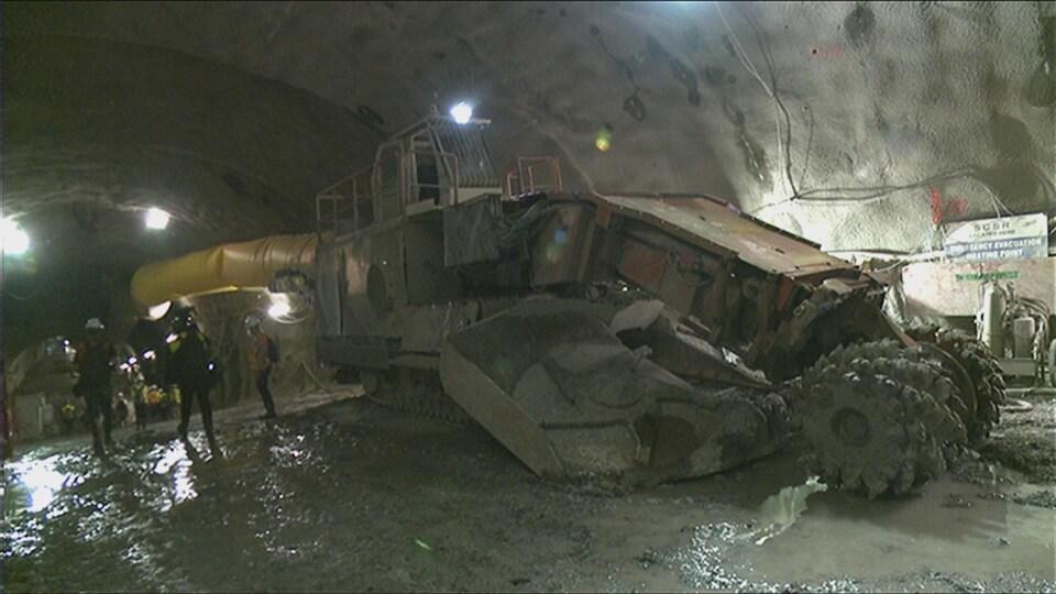 Une excavatrice dans un vaste tunnel éclairé.