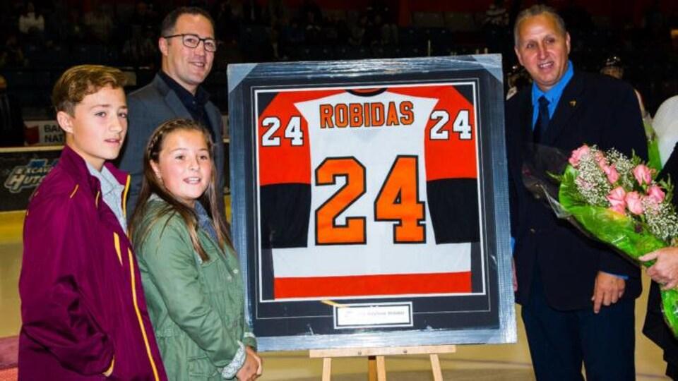 Stéphane Robidas avec ses enfants à côté de son chandail de hockey qui a été retiré.