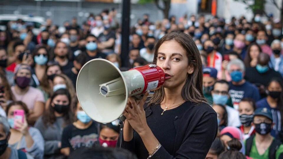 Une femme parle dans un mégaphone devant une foule.