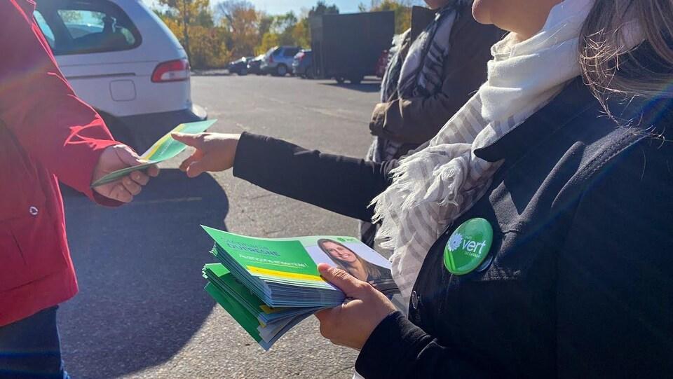 La candidate Stéphanie Dufresne qui remet un dépliant à un électeur.