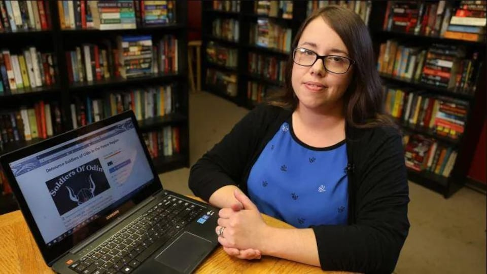 Stephanie Goudie porte des lunettes assise devant son ordinateur devant une bibliothèque.