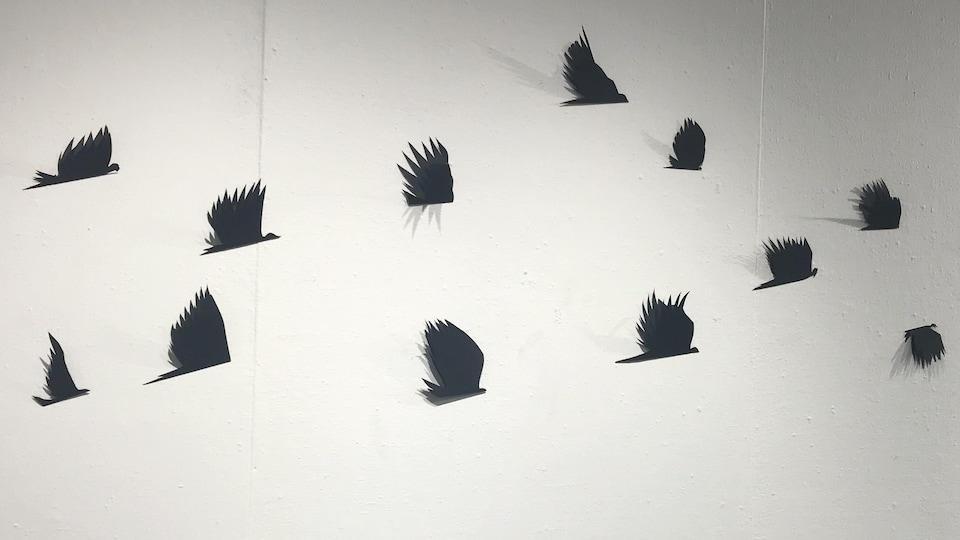 Une envolée d'oiseaux découpés dans du papier noir.