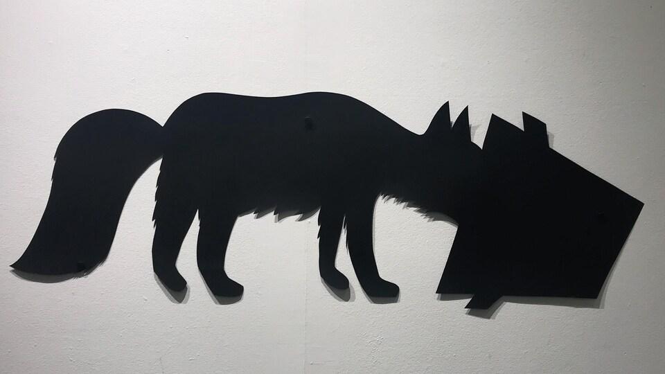 Un renard découpé dans un papier noir, mange dans une poubelle.