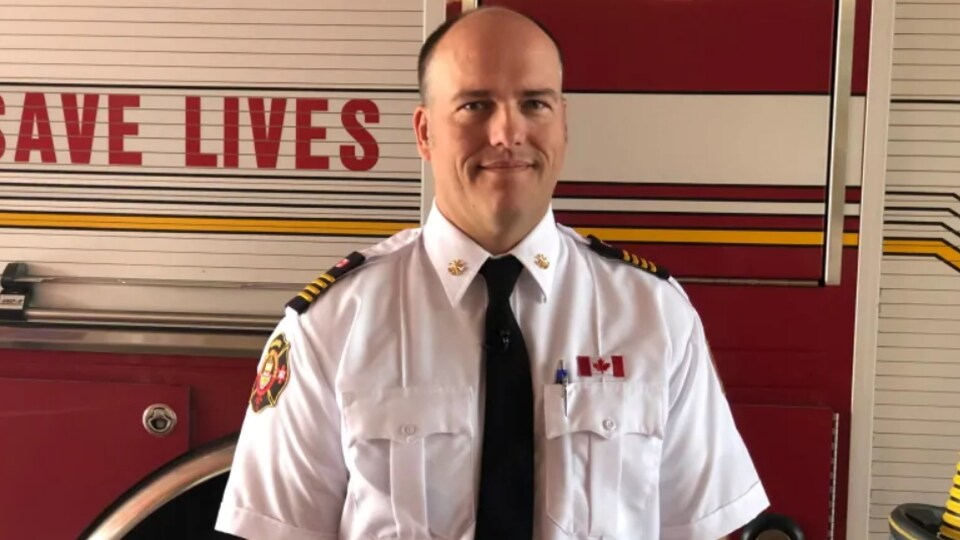 Stephen Barkwell, chef adjoint des pompiers à Oshawa, pose devant un camion de pompiers à l'intérieur d'une caserne.