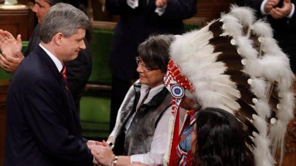 L'ancien premier ministre canadien, Stephen Harper, en compagnie d'un autochtone arborant une coiffe traditionnelle, en 2008