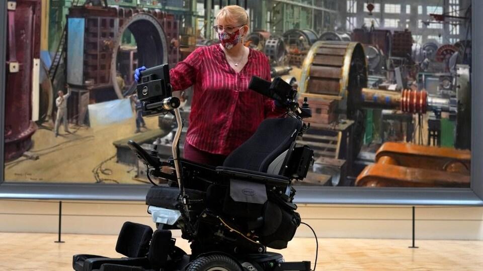 La conservatrice Kate Perks pose avec le fauteuil roulant utilisé par le Pr Stephen Hawking.