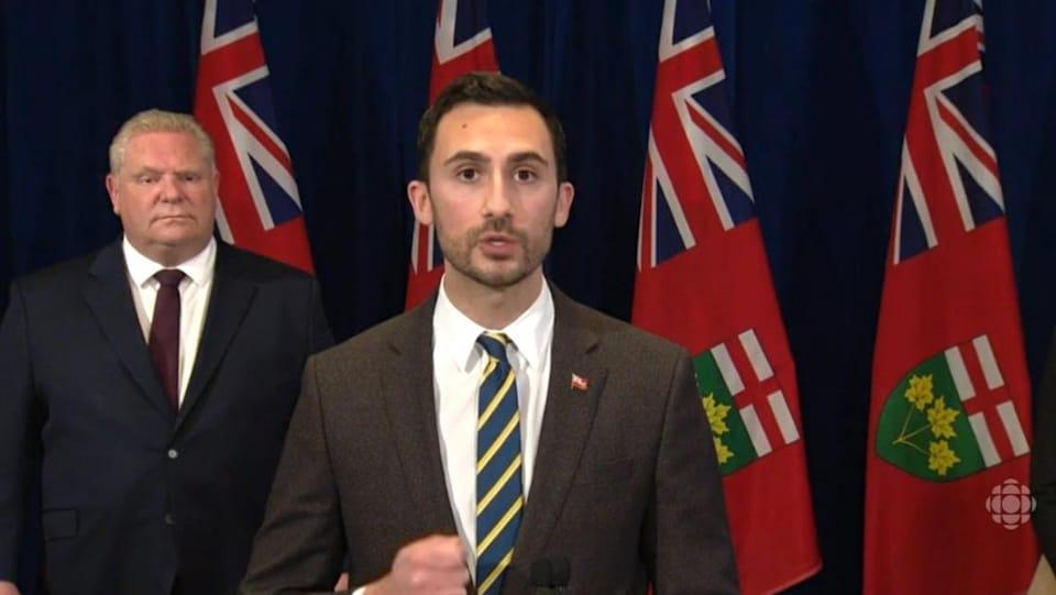 M. Lecce parle debout au micro alors que le premier ministre Doug Ford se tient en retrait à l'arrière.