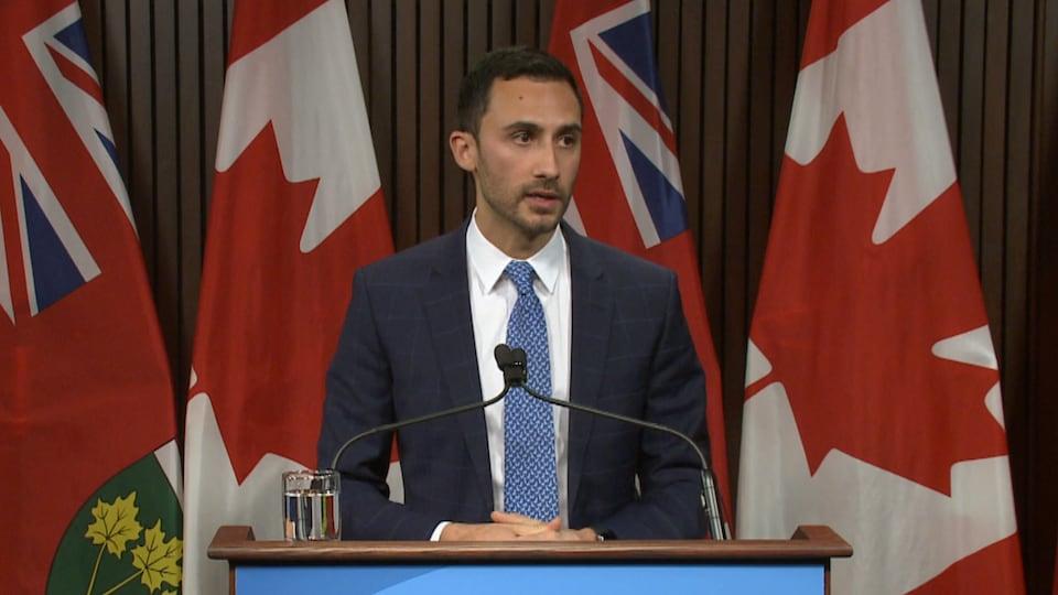 Un homme sur un podium en conférence de presse.