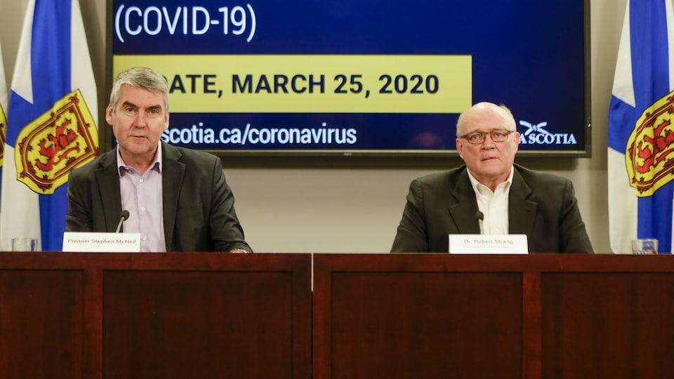 Deux hommes devant un écran géant affichant des informations sur le coronavirus.