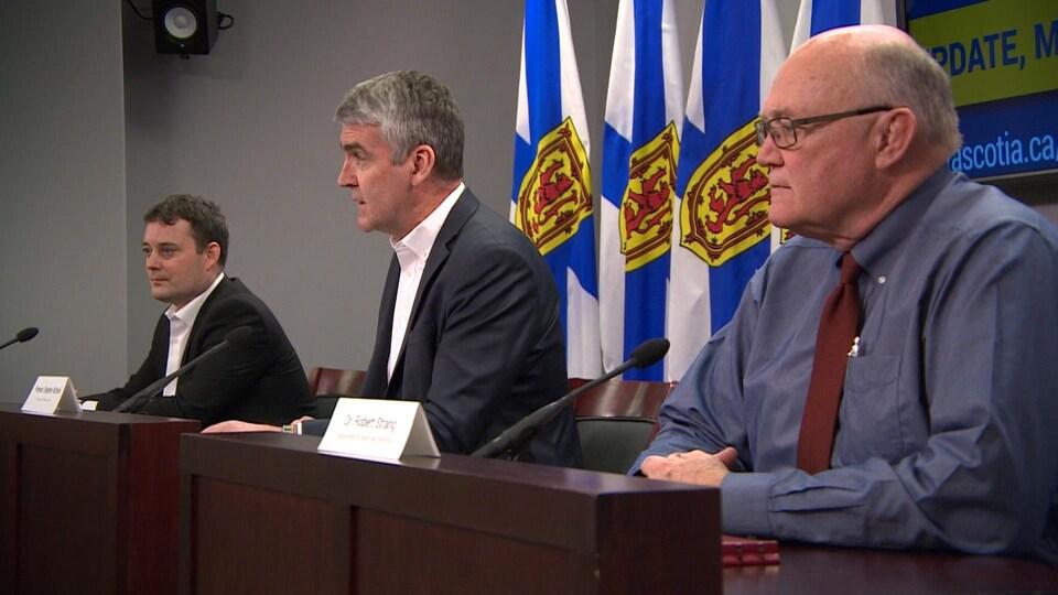 Trois hommes en conférence de presse, vu du côté droit de l'estrade.