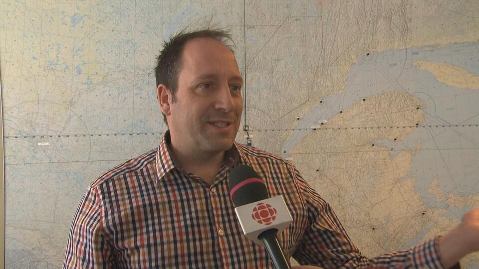 Un homme en entrevue à Radio-Canada devant une carte du Québec.