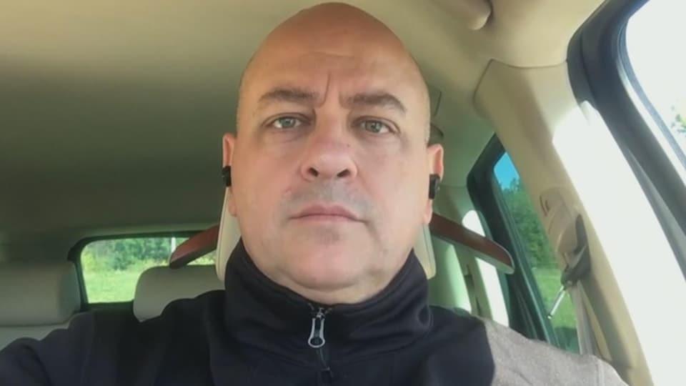 Un homme, pendant une entrevue par visioconférence, regarde droit dans l'objectif. Il est dans sa voiture.
