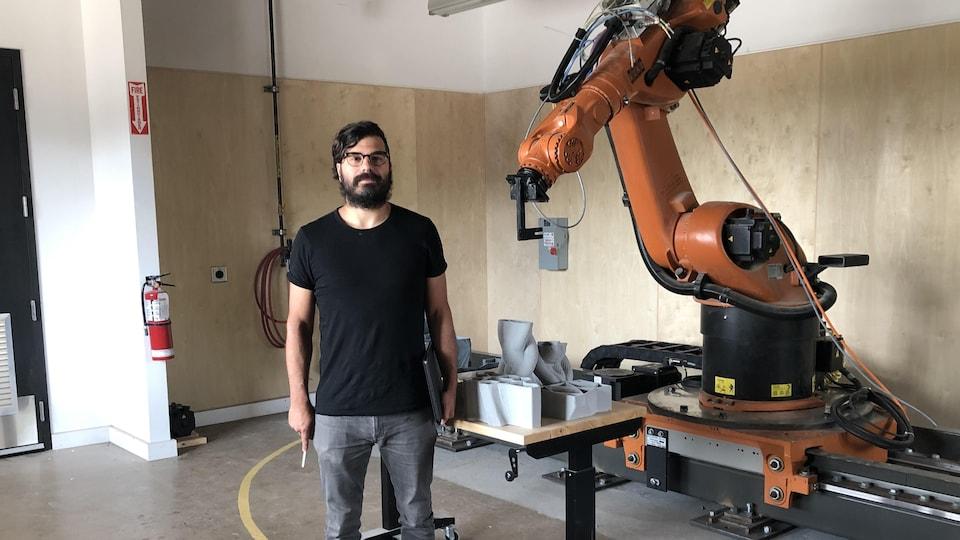 Le professeur de science et d'architecture Steven Beites avec un robot installé dans un atelier de l'École d'architecture McEwen.