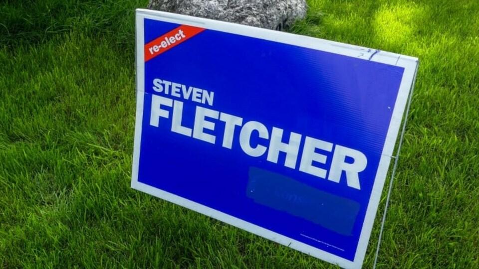 Une pancarte de campagne bleue, au nom du Steven Fletcher, où le logo du Parti conservateur du Canada a été recouvert.