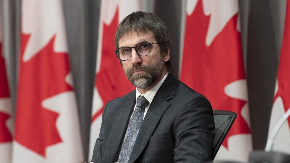 Steven Guilbault devant une rangée de drapeaux canadiens.
