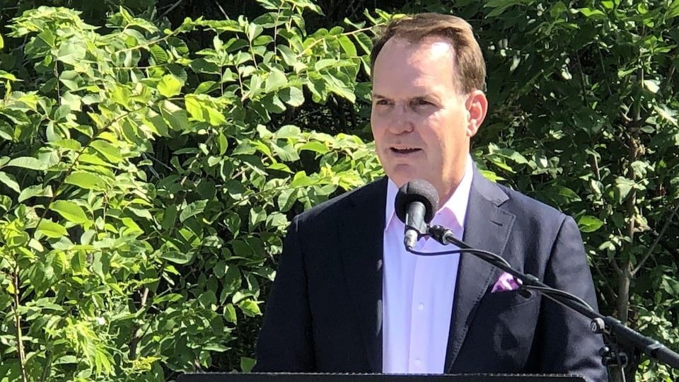 Steven MacKinnon, pendant une conférence de presse, devant des arbres.