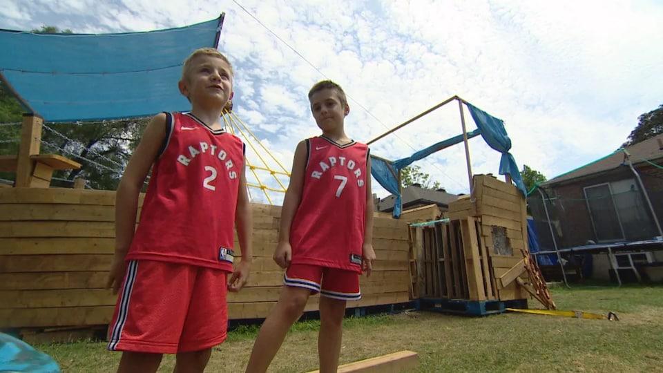 Steven et Michael se tiennent devant le bateau en bois.