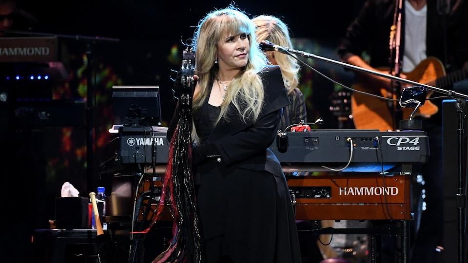 Stevie Nicks debout sur scène face au public, deux musiciens derrière elle.