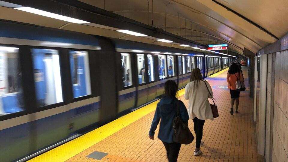 Des gens marchent sur le quai du métro, alors qu'un train passe.