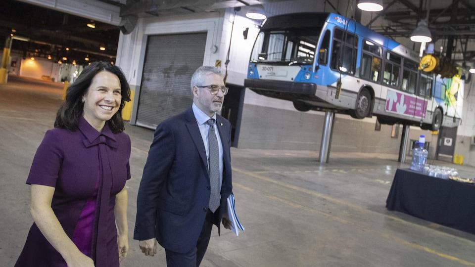 Ils marchent dans un garage avec en arrière-plan un autobus suspendu.