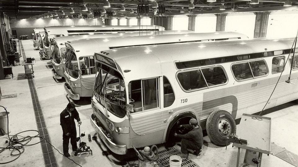 Des mécaniciens font des réparations sur les pneus d'un autobus dans le garage de la Société de transport de l'Outaouais en 1974