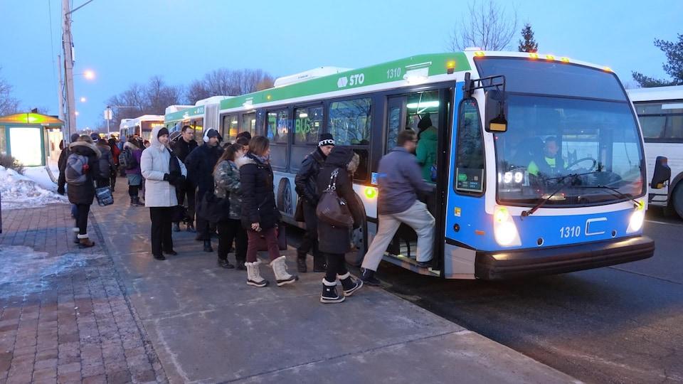 Des usagers du transport en commun montent dans des autobus.