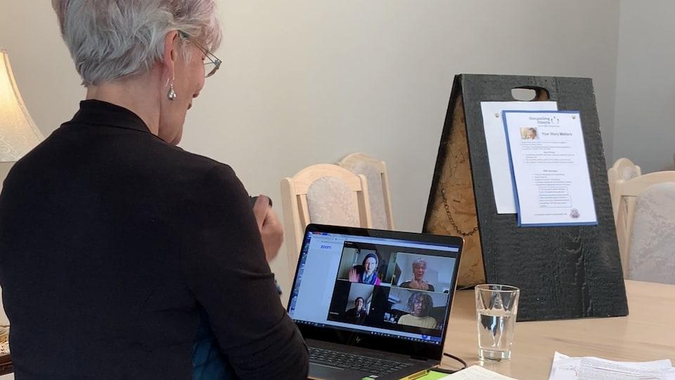 Une femme est en télé-conférence avec trois autres personnes devant son ordinateur.