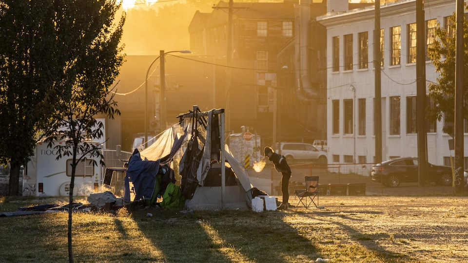 A person stands outside of a tent at the Strathcona park homeless camp in Vancouver, British Columbia on Monday, September 28, 2020.