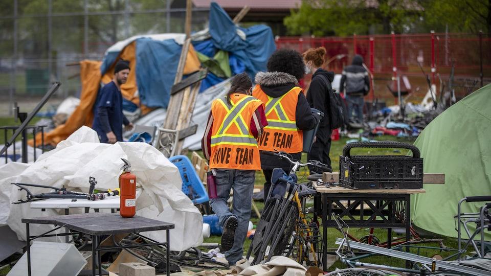 Des employés avec un gilet orange marchent dans un parc de tentes.