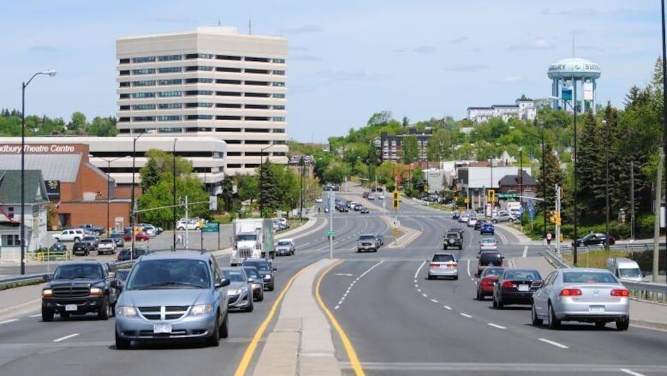 Une rue du centre-ville de Sudbury. Les voitures sont en mouvement.