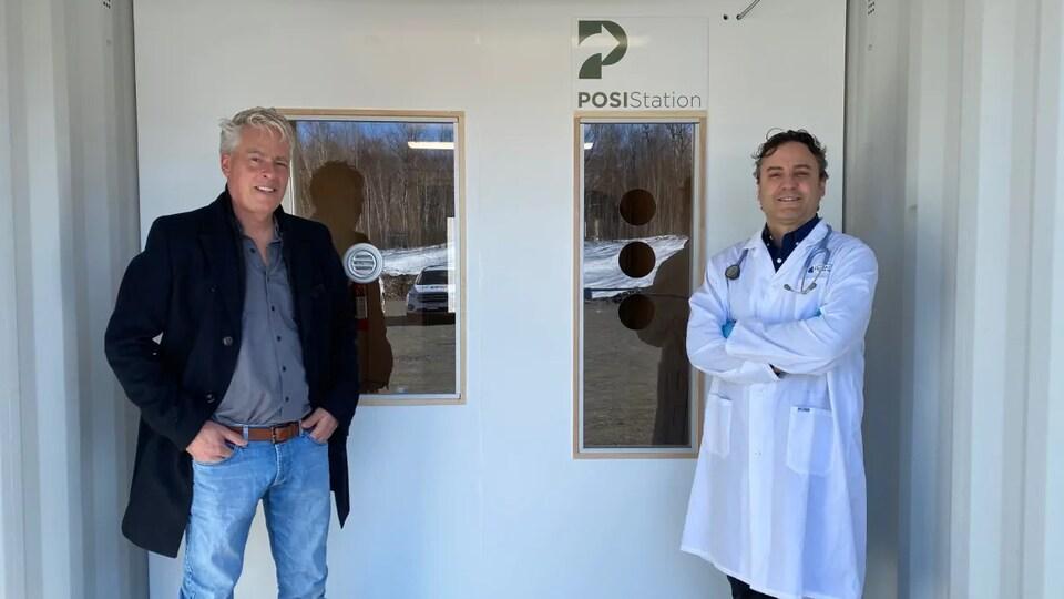 Deux hommes se tiennent debout dans un conteneur converti avec des fenêtres à l'intérieur