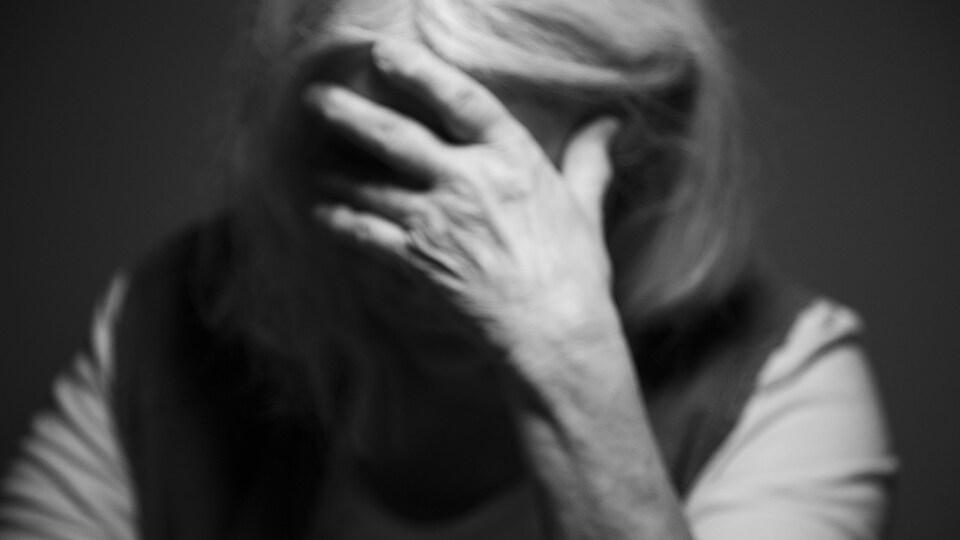Une femme se prend la tête avec sa main.