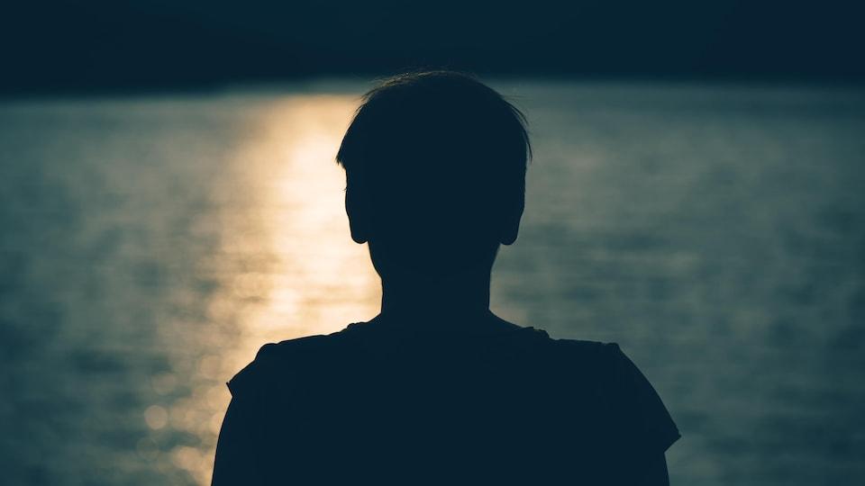 Silhouette d'un jeune déprimé devant un cours d'eau.